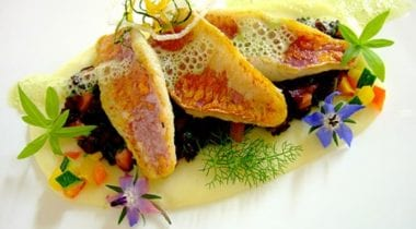 Mullet fillets and black rice with pistachio on sweet and sour sauce with pine nuts and mandarin orange